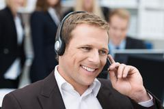 businessman taking a call on a headset - stock photo