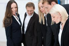 Attractive blond businesswoman with her team Stock Photos