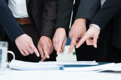 Group of businesspeople pointing to a document Stock Photos