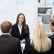 Smiling female boss or team leader Stock Photos