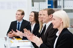 smiling business people clapping their hands - stock photo