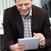 smiling man using a tablet-pc - stock photo