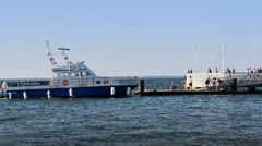 Ferry leaving pier with crowd - pan Stock Footage