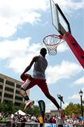 Man attempts reverse jam in outdoor slam dunk competition Stock Photos