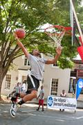 man attempts slam dunk during outdoor street basketball tournament - stock photo