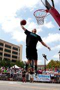 Man leaps to jam basketball in outdoor slam dunk contest Stock Photos