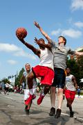 Man shoots against defender in outdoor street basketball tournament Stock Photos
