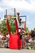 young man jumps high in outdoor basketball slam dunk contest - stock photo