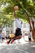 young man leaps to dunk basketball during outdoor street tournament - stock photo