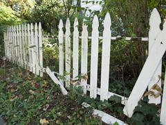 White picket fence falling apart Stock Photos