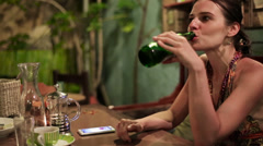 Pensive sad attractive woman drinking beer in cafe HD - stock footage