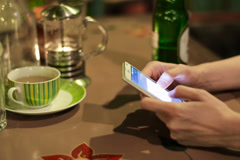 Woman hands typing on touch screen smartphone in bar NTSC Stock Footage