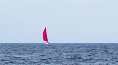 Yacht with a red sail on the sea - stock footage