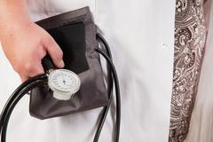 doctor with blood pressure measuring tool - stock photo