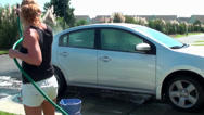 Stock Video Footage of Woman rinsing off the car