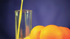 Three oranges and  juice which is pouring in  glass Stock Footage