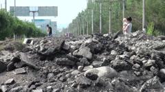 People walk through pile of asphalt in Bishkek, Kyrgyzstan Stock Footage