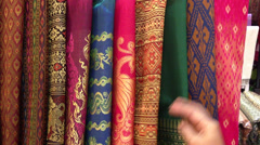 Young woman shopping for silk Thai - stock footage
