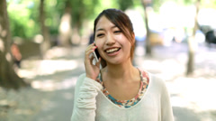 Asian woman walking talking on cellphone on a city street - stock footage