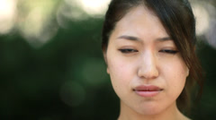 Asian woman sad concerned face sitting on a park bench Stock Footage