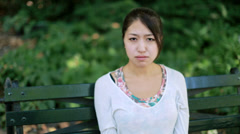 Asian woman sad concerned face sitting on a park bench - stock footage