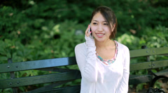 Asian woman calling talking on cellphone smartphone sitting down park bench - stock footage