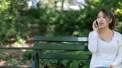 Asian woman talking on cellphone smartphone sitting down park bench - stock footage
