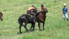 Two men wrestling on horseback in Kyrgyzstan, nomadic tradition in Central Asia Stock Footage