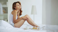 Lovely brunette luxuriating in bed in the morning - stock footage