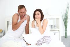 Tired young couple yawning in bed Stock Photos