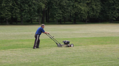 Worker moves with lawnmower and mows green grass Stock Footage