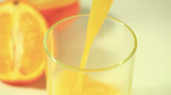 Orange juice flows in a glass with silhouettes of fruit Stock Footage