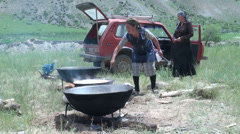 Women prepare bowls of soup in Kyrgyz village Stock Footage