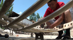 Worker prepares wooden yurt in small factory Kyrgyzstan Central Asia Stock Footage