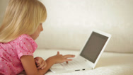 Stock Video Footage of Beautiful little girl lying on sofa using laptop and smiling at camera