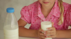 Charming little girl drinking milk and smiling at camera Stock Footage