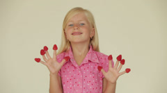 Funny little girl with raspberries on her fingers smiling at camera Stock Footage