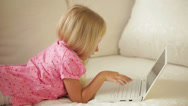 Stock Video Footage of Cute little girl lying on sofa using laptop and smiling