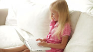 Stock Video Footage of Cute little girl sitting on sofa with laptop and smiling at camera