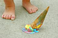 Dropped ice cream cone by child's feet Stock Photos