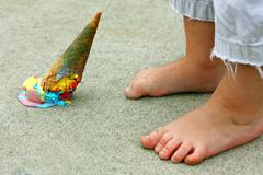 Dropped ice cream cone by feet Stock Photos