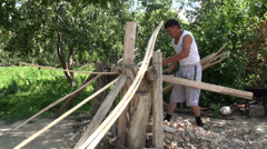 Woodworker in Kyrgyzstan, scraping trees to make a traditional yurt Stock Footage