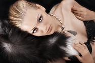 Stock Photo of sexy blonde laying on black just wearing fur