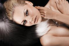 blonde model laying on fur - stock photo