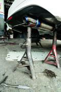 Car 's changing new exhaust pipe on tripod hand jack. Stock Photos