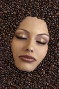 girl's face immersed in coffee beans - stock photo
