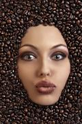 portrait of a pretty girl laying among coffee beans - stock photo