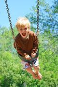 Stock Photo of child swinging at park