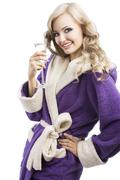 blond haooy girl in bathrobe drinking champagne, she looks in o the lens and  - stock photo