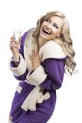 blond haooy girl in bathrobe drinking champagne, she laughs and looks up - stock photo